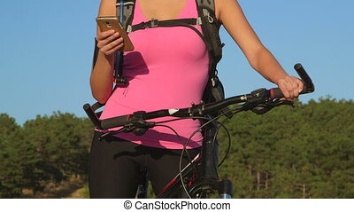Active woman cyclist on bicycle using smart phone during cycling workout outdoors