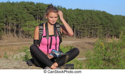 Hiking young woman looking at map during hike trekking in forest