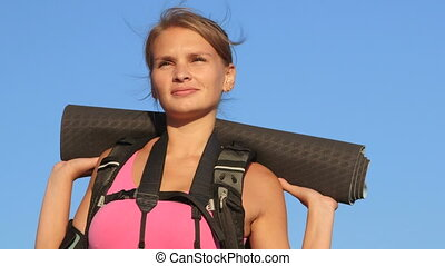 Face of hiking young woman during hike trekking against blue...