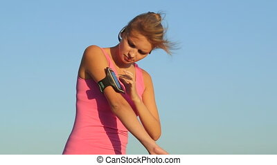 Fitness young woman touching phone screen in arm sport band...