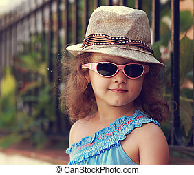 Modern kid girl in fashion glasses and hat looking happy on...