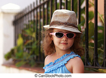 Fashion kid girl in glasses and hat outdoors background....