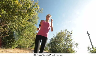 Fit sports girl jogging along country road during outdoor...