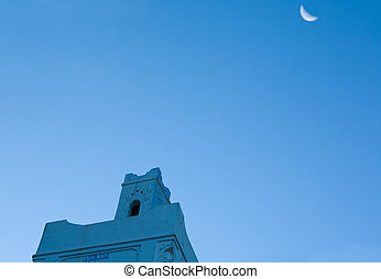 Mosque in Chefchauen with moon - Sunrise silhouette of...