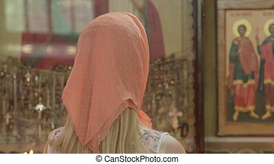 Young woman worshipper praying in Christian Orthodox Church...
