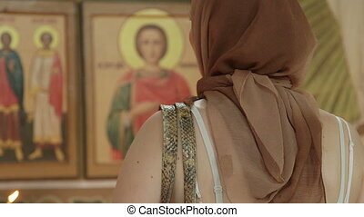 Christian woman praying before icon in Orthodox Church