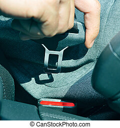 man fastening the car safety belt