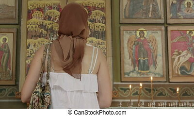 Christian women prayer before icons in Orthodox Church -...
