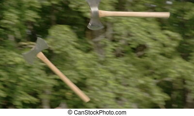 Two axes flying and thrown on the logboard. There is an axe...