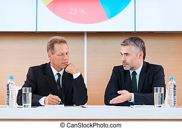 Preparing to presentation. Two confident business people in formalwear discussing something with large monitor upon them
