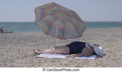 Overweight woman lying  on the beach