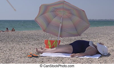 Overweight senior woman in swimsuit lying on summer beach