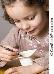 Girl eating yogurt - Little girl eating yogurt / yoghurt