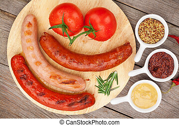 Various grilled sausages with condiments and tomatoes on...