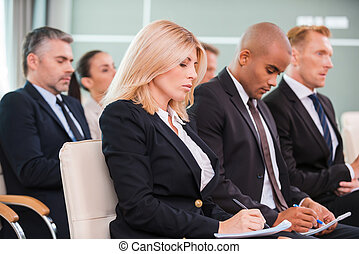 People at the conference. Group of business people in...