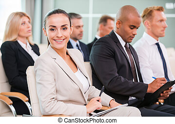 Woman at the conference. Group of business people in...