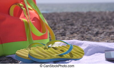 Colorful bag flipflops and towel at summer beach
