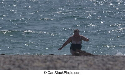 Overweight senior woman in swimsuit after swimming on the beach