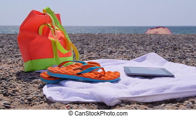 Beach bag flip flops towel and tablet computer at summer...