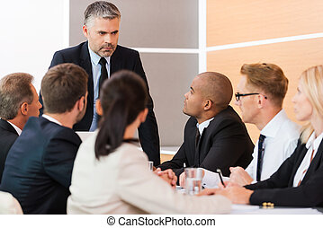 Urgent business meeting. Business people in formalwear sitting at the table together while their boss standing and looking at them
