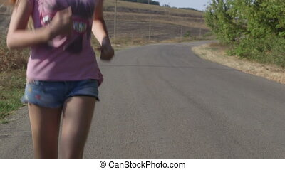 Girl running along a country road