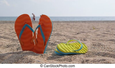 Pair of flip flops on a sandy beach in summer close-up