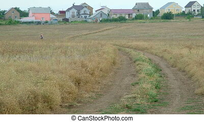 Girl riding horse on dirt road through the field