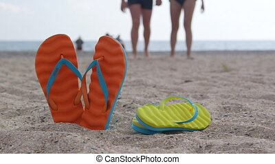 Couple summer beach vacation getaway flip flops in the sand...