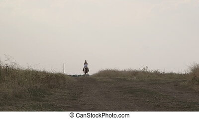 Young girl riding horse down the trail in countryside