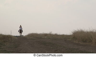 Young woman rider riding horse far away on dirt road