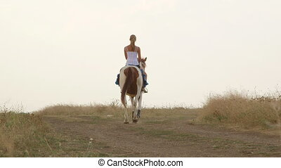 Young girl riding horse in countryside