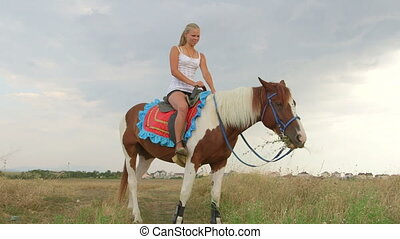 Horseback riding vacations young girl in saddle feeding...