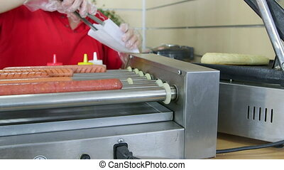 Employee making top loader hot dog in fast food takeout...