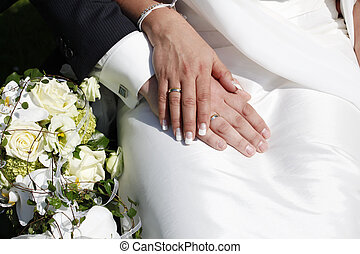 wedding rings on hands, beside the bridal bouquet