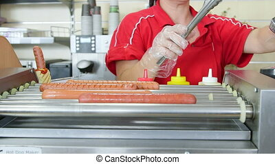 Woman employee prepares hot dogs in a fast food restaurant -...