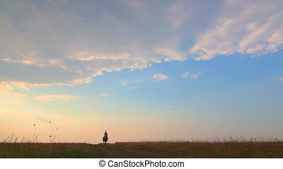 Young girl riding horse across the field in evening