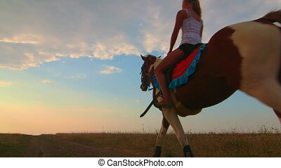 Horseback riding to the horizon at sunset