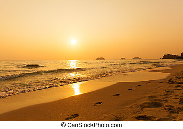 Beautiful sunset above the sea. Footprints in the sand.