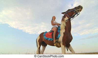 Horseback riding vacations young girl in saddle wide angle