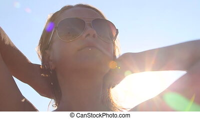 Young girl wearing aviator sunglasses after swimming in sunshine at the beach