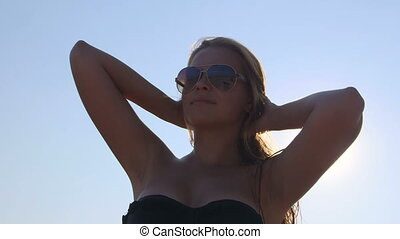Young girl wearing aviator sunglasses after swimming in...