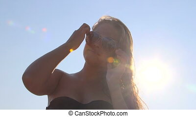 Smiling young girl in sunglasses against the sun