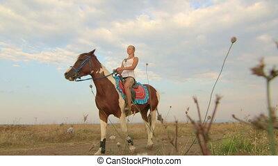 Girl rides a horse through the field