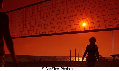 Young couple playing volleyball on summer beach at sunset