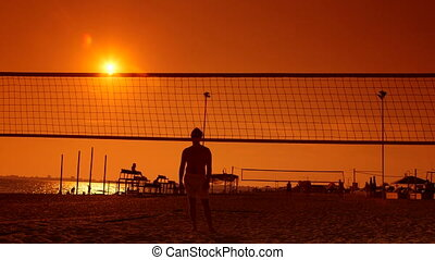 Friends playing volleyball on beach at sunset