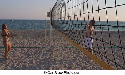 Young couple spend a weekend playing beach volleyball