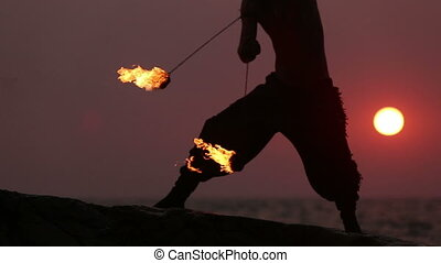 Male Artist of the spins fire poi on a rock at sunset on a...