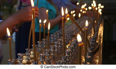 Faithful people lighting prayer candles in the church close-up