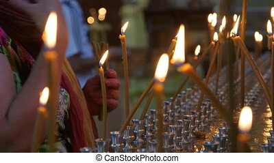 Woman lighting prayer candle in Christian Orthodox Church