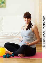 Gravid woman taking break from fitness exercises - Portrait...